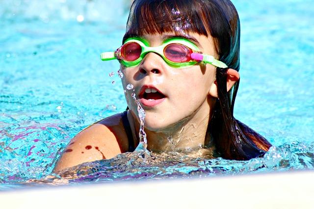 Swim teacher talking to child in water