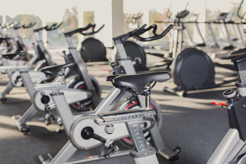 Modern gym interior with equipment. Fitness club with row of training exercise bikes. Healthy lifestyle concept