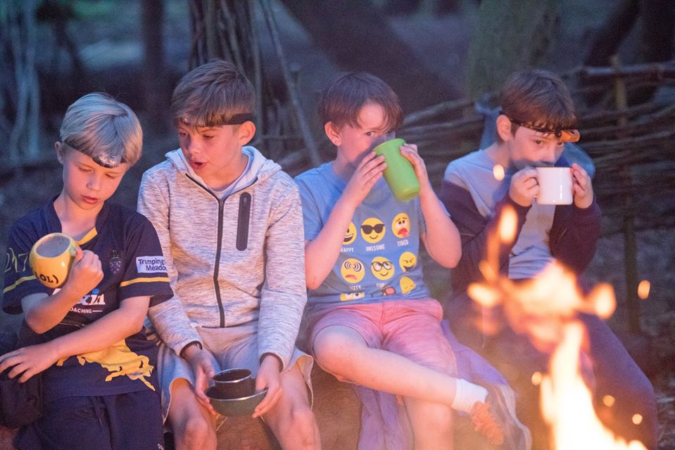 Children drinking by a camp fire
