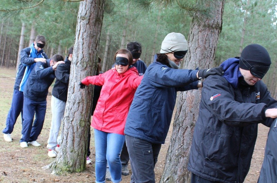 Young people playing a team building game, blindfolded