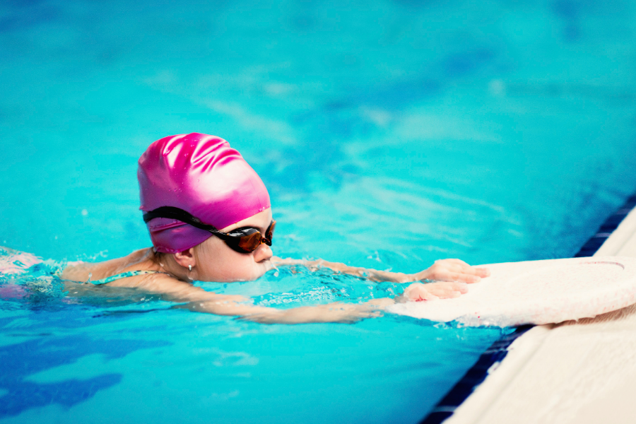 child in pink hat swimming