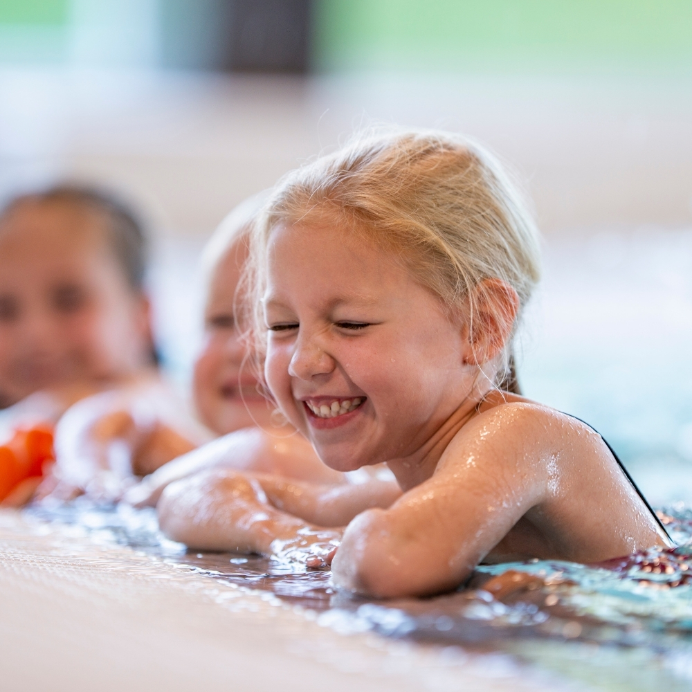 Little girl laughing at side of pool