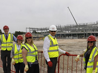 People looking at construction site steelwork at Mildenhall Hub
