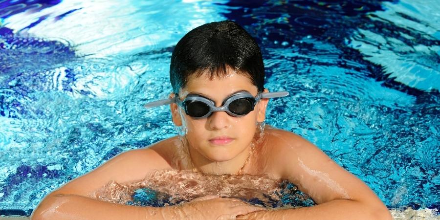 teenage boy in water at poolside