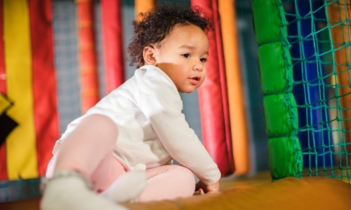 toddler on soft play equipment