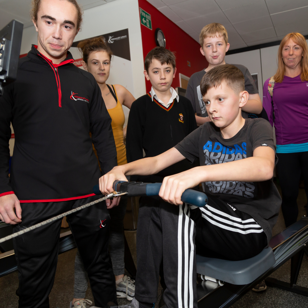 Child using rowing machine with on lookers